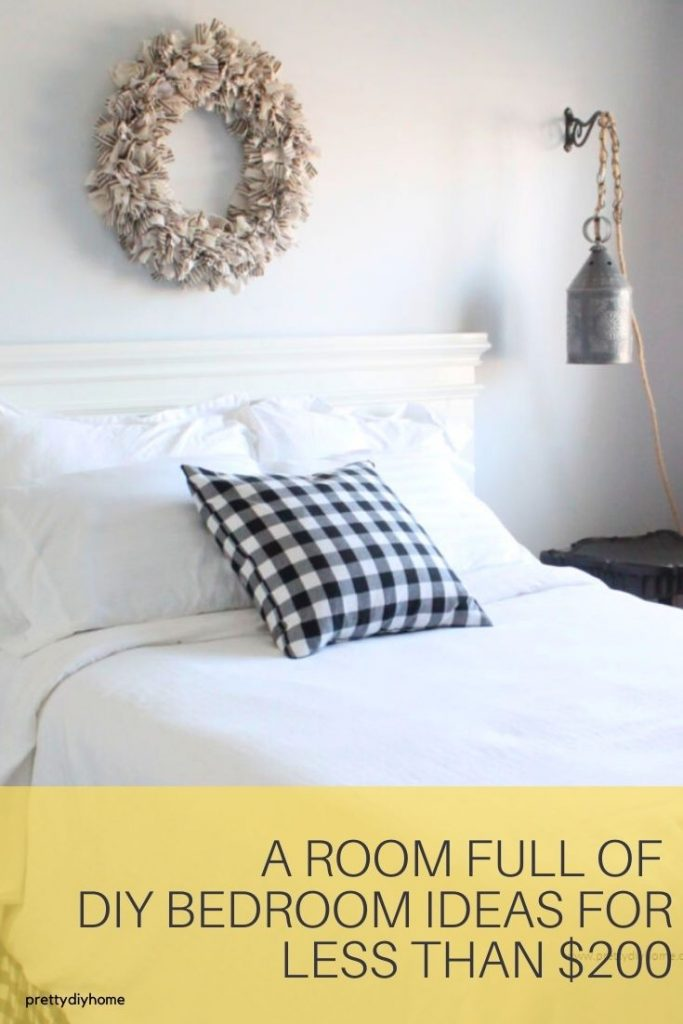 A black and white farmhouse bedroom full of DIY Bedroom Ideas including a hand made bed, and wreath.