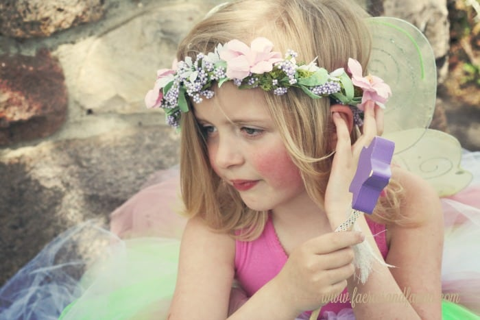 A little girl with flowers in her hair, wings and a start shaped fairy wand. fairy crown DIY, DIY tiara, DIYprincess crow, DIY crown, fairy crowns and tiaras, fairy wreath headpiece,fairy party, children's wedding outfit, children's party,forest fairy tutu, fairy costume, tutus for girls fairy tutu diy fairy tutu, no sew tutu, no sew fairy tutu