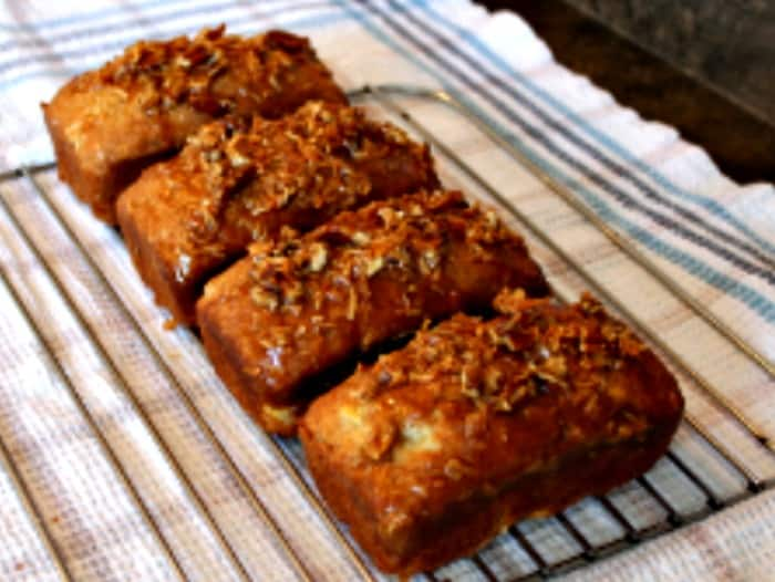 Banana loaf recipe with coconut and lime glaze cooling on a rack. This is a ultra moist banana bread