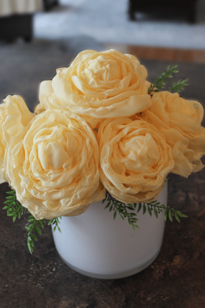 A large bouquet of fabric peonies in soft yellow.