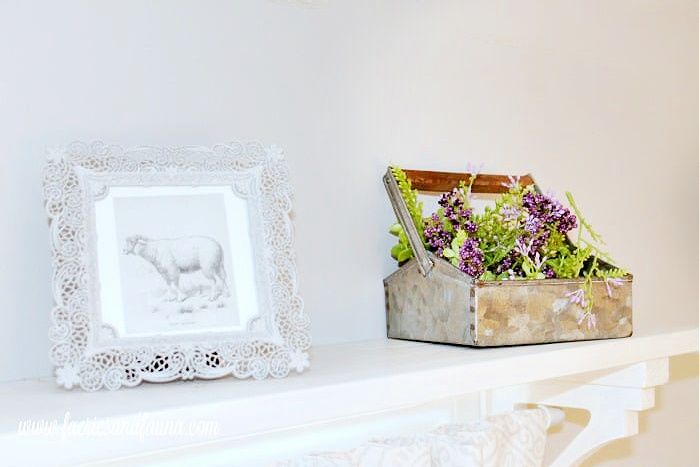 Two small pieces of farmhouse decor, one is a small picture frame, and the other is a small galvanized container holding greenery. The two accessories are sitting ontop of a DIY window shelf curtain rod combo made from wood and painted white.