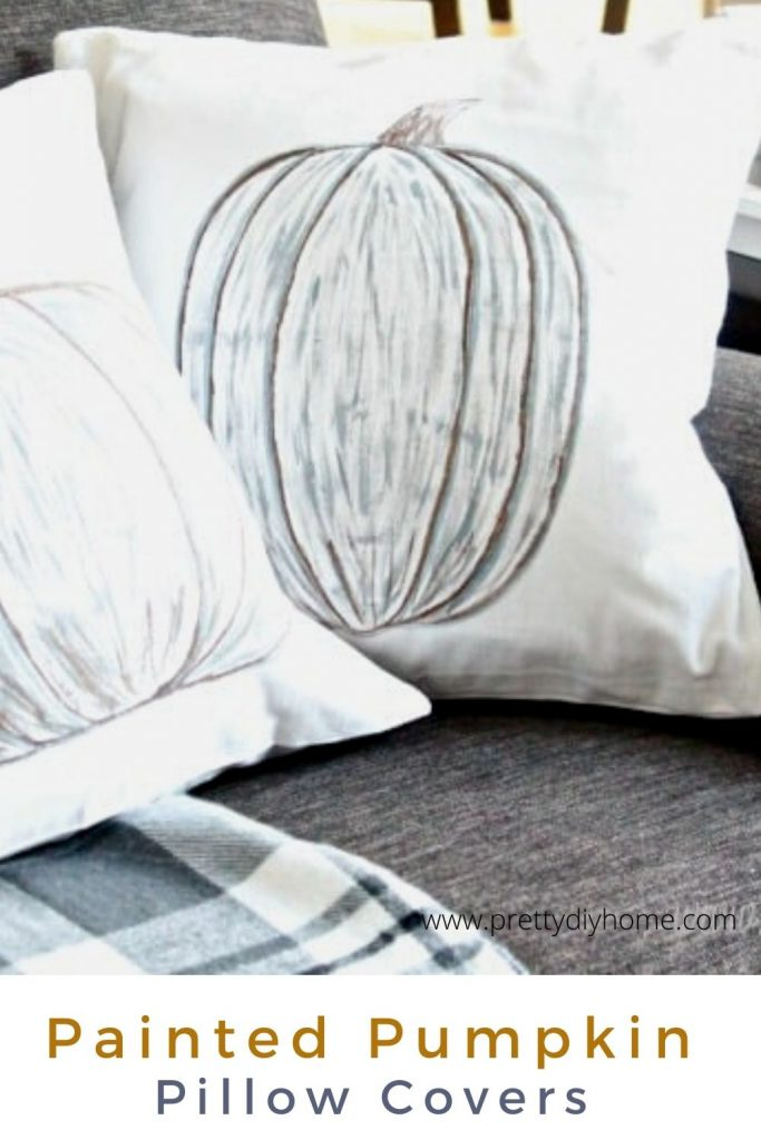 A white pillow cover with neutral hand painted pumpkin.