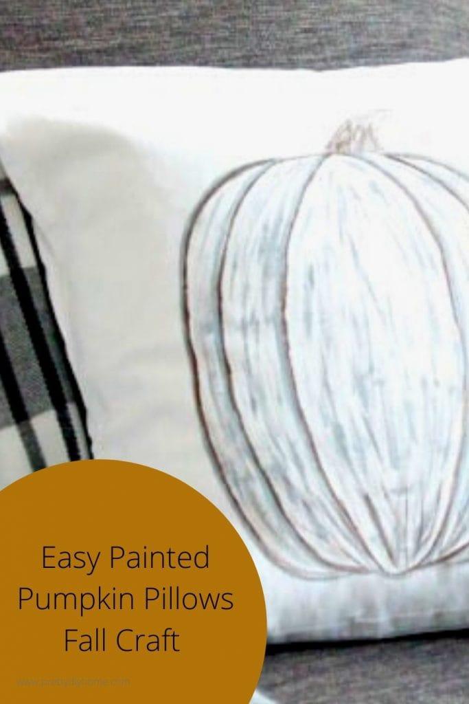 DIY neutral Fall pumpkin cushion with a black and white plaid coverlet.