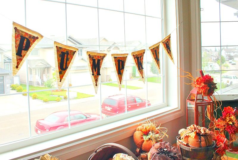 A large front window display for fall with a handmade fall pumpkin banner.
