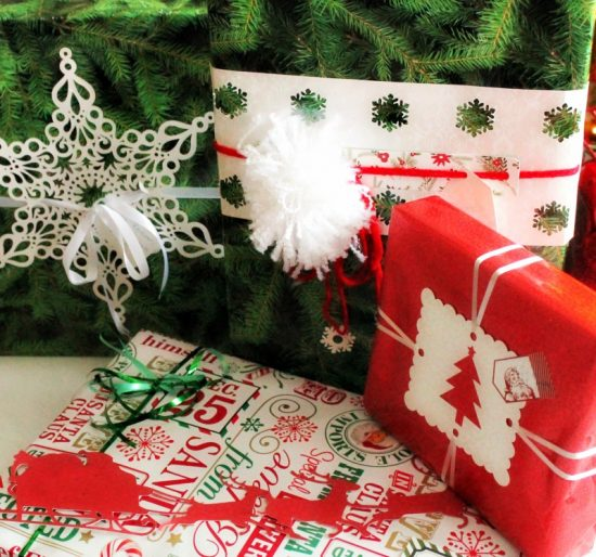Beautiful Christmas wrapped gifts for in the mail with pom poms, snowflakes and pretty Christmas paper.