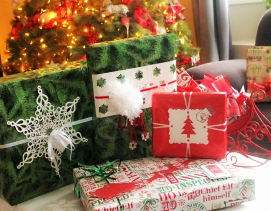 Pretty wrapped gifts for in the mail, with snowflakes pom poms and pretty Christmas wrapping paper.