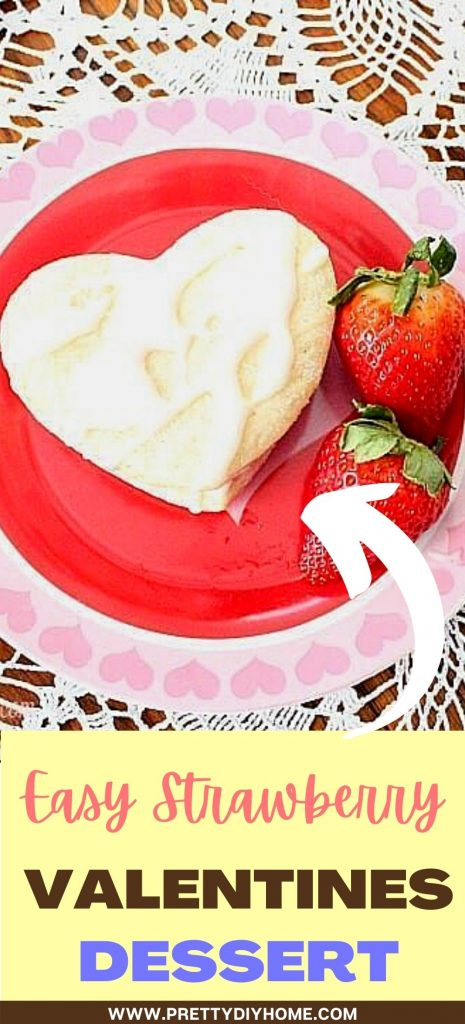 A heart shaped ice cream sandwich with vanilla glaze, sugar cookies and strawberry ice cream on a pretty Valentine plate.