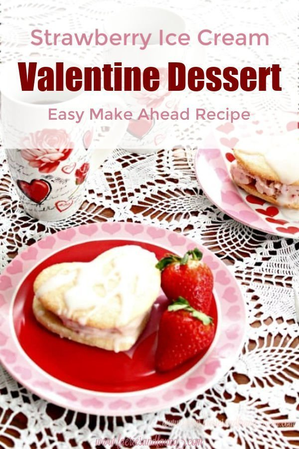A homemade ice cream sandwich made with two heart shaped lemon sugar cookies and strawberry icing cream. Its covered in a vanilla glaze and sitting on a valentine plate with fresh strawberries on the side.