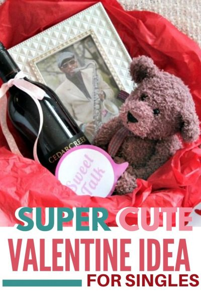 A basket full of Valentine gift ideas for a girlfriend including a bottle of wine, a teddy bar some love noted and a photograph.