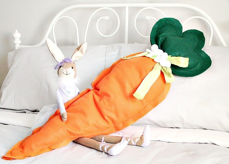 Large stuffed Easter cushion in the shape of a carrot being held by a bunny.