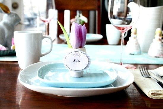 A Easter brunch tablesetting idea using decorated Easter egg place holders and fresh Spring flowers.