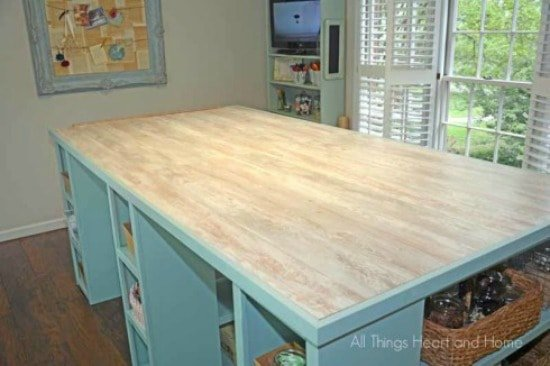 A large DIY craft room table with various cubicles, shelves and storage areas for crafts and hobbies. Craft room ideas, craft room ideas on a budget, hobby room idea, sewing room idea, craft area ideas,craft room inspiration, home office craft room ideas.
