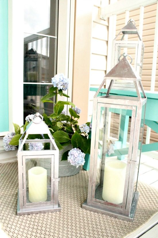Three front porch lanterns or patio lanterns with a galvanized finish and candles.  Beautiful outdoor decor.   How to paint a galvanized finish, DIY garden lantern, lantern update, DIY lantern