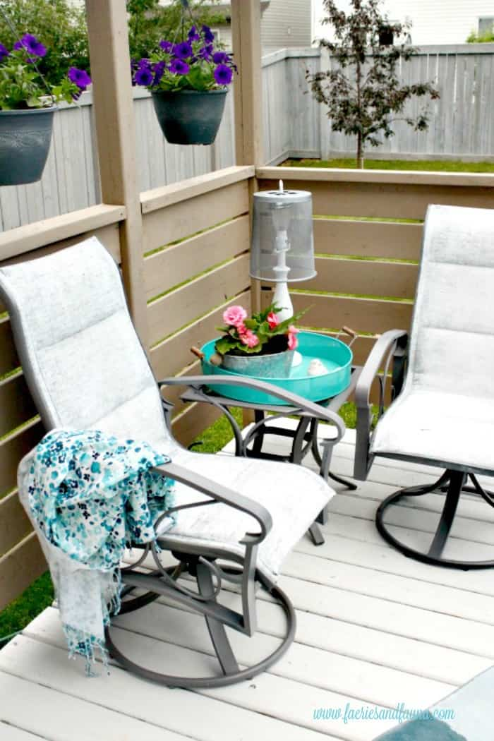 Outdoor patio furniture makeover using white paint on two captain chairs as part of a larger ombre patio set.