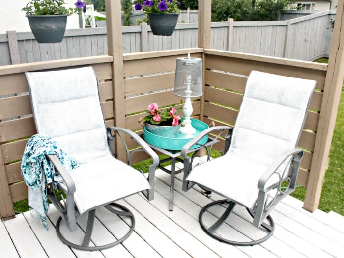 The back corner of a small garden tour featuring DIY repainted patio furniture and turquoise accessories.