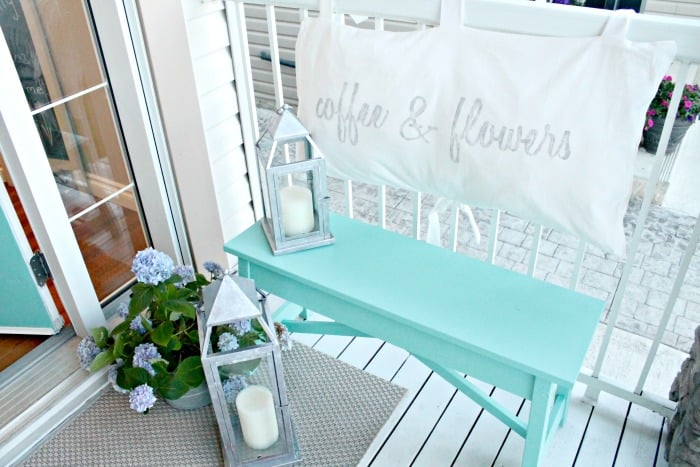 The front porch of a small yard garden tour, with DIY turquoise bench and flowers.