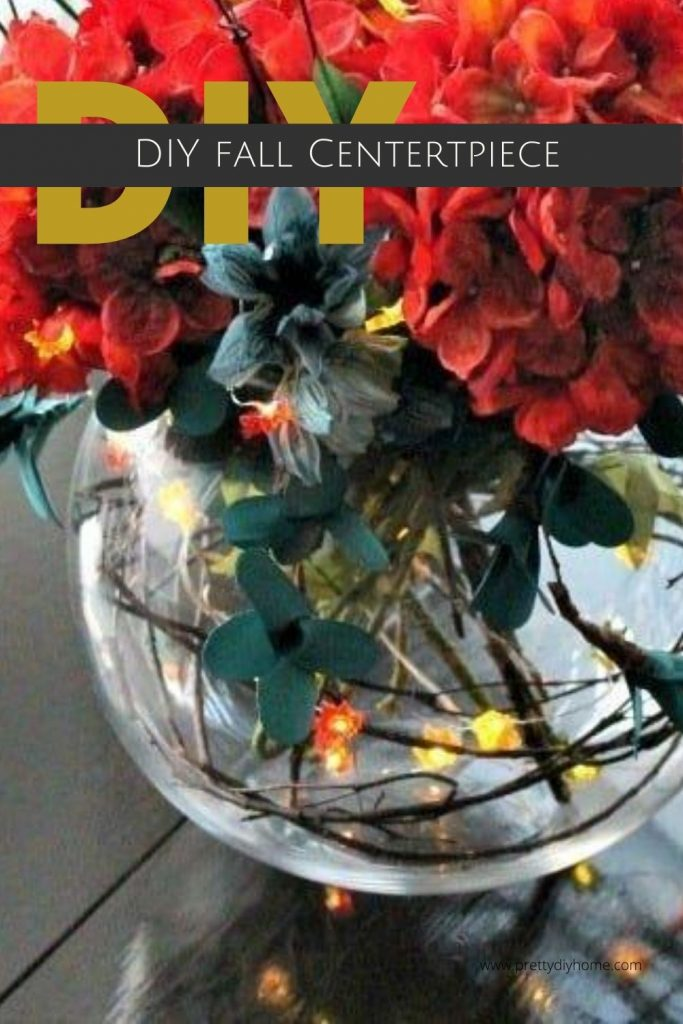 DIY Fall Centerpiece with orange and teal flowers in a glass vase with fairy lights sitting on a kitchen tabl.e
