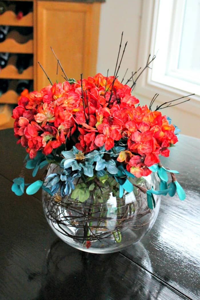 A fall centerpiece made with orange and blue florals, brown twigs and coloured fairy lights.