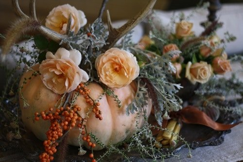 Elegant fall decorating idea, floral arrangement with antlers and pumpkin