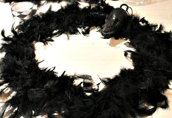Wrapping dollar store feather boa around a wire wreath from to make a Halloween Wreath.