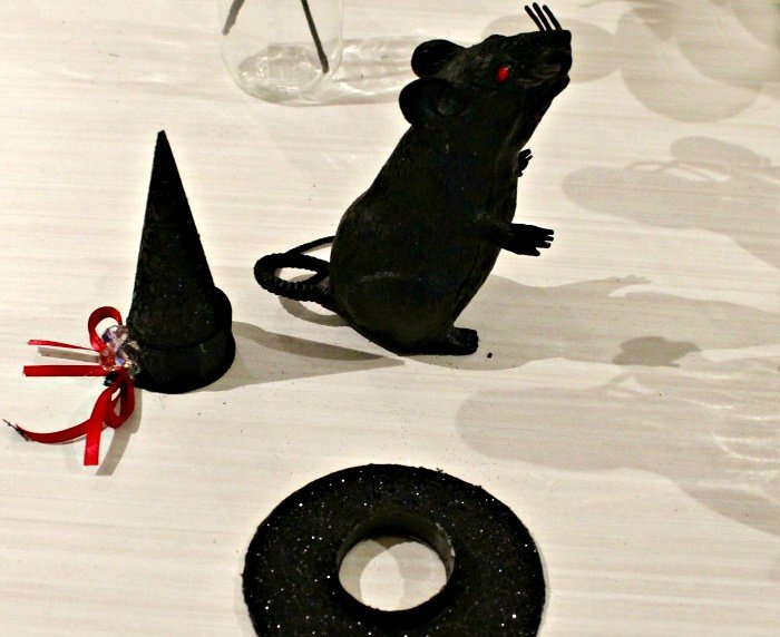 Adding a hat to a Dollar store rat as a centerpiece on a Dollar store wreath for Hallowee.
