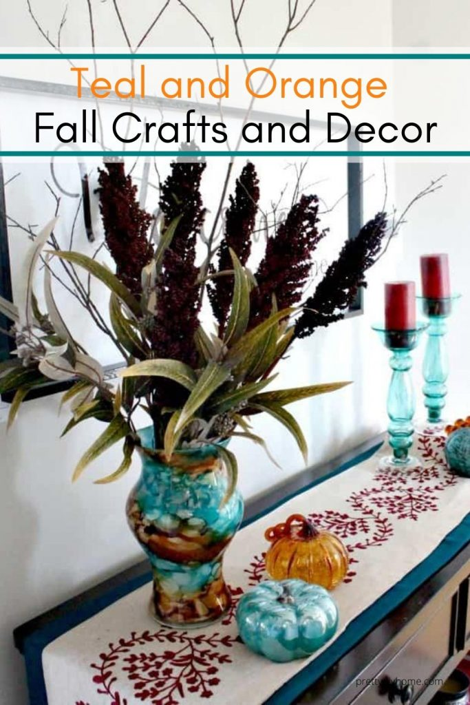 A tall vase on a front foyer table with DIY Fall candles, flower arrangements, and handmade table runners.