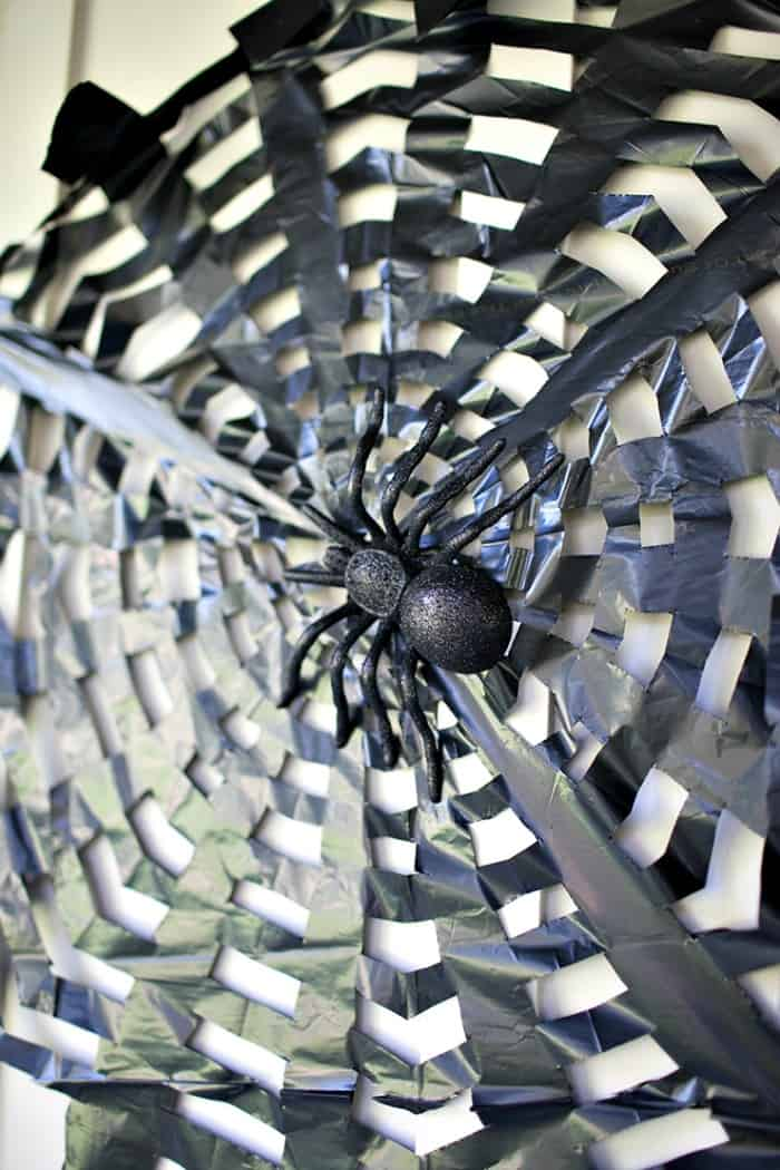 DIY spider web made out of garbage bags for he front door on Halloween. DIY Halloween front porch ideas, Halloween porch displays, DIY Halloween yard decorations, DIY Halloween front porch ideas, DIY Halloween front door decorations,