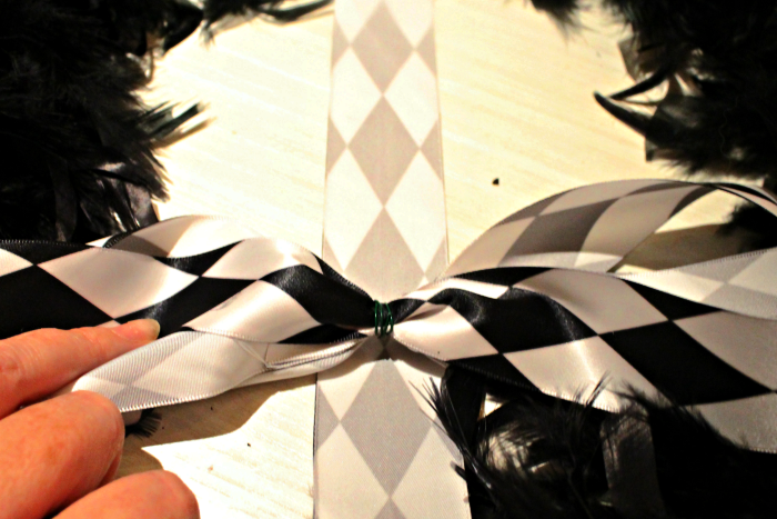 Tying a harlequin fabric ribbon onto a Dollar Store Craft Wreath for Halloween.