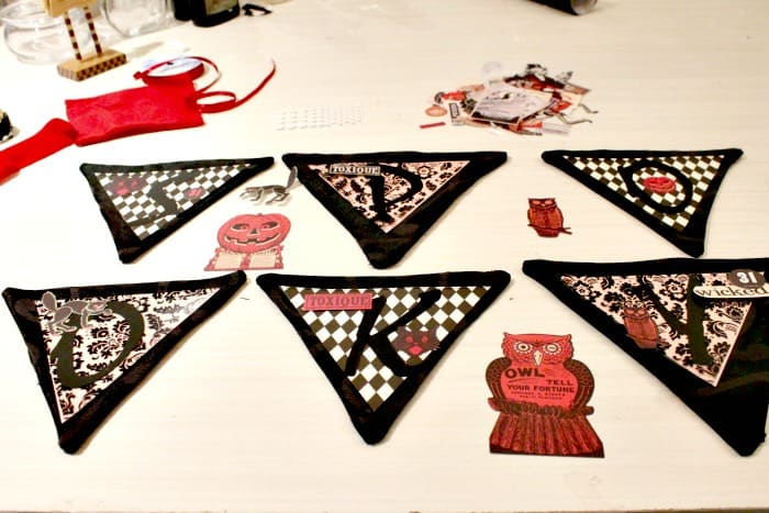 A DIY Halloween banner that is classy and not too scary. It features unique colours for Halloween, black, red, and white. With red velvet ribbons and harlequin paper banner diamonds.