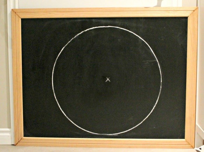 Drawing a circle to start the moon on Halloween Chalkboard Art. A DIY Halloween decoration or Halloween project. This project is not scary.