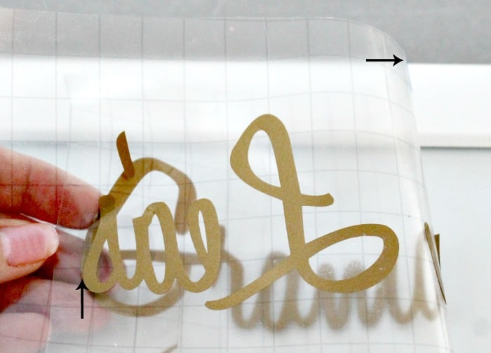 Vinyl lettering being applied to a DIY farmhouse sign for the kitchen that says Bakery. farmhouse kitchen, farmhouse style kitchen, farm style kitchen,farmhouse kitchen accessories
