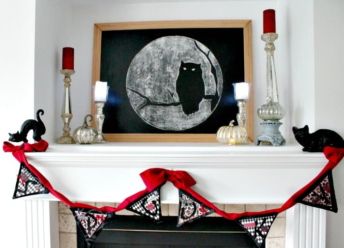A classy Halloween decorating idea. A DIY Halloween mantel decorated with metallic candlesticks, red velvet, black cats. A Halloween decor idea for older adults.