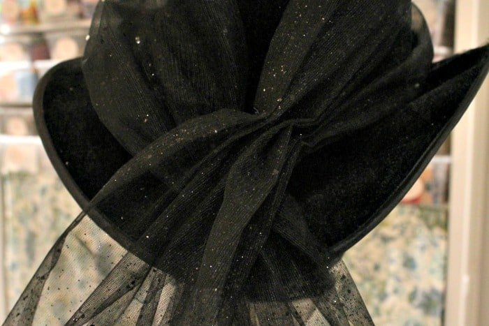 Adding embellishment to a not scary witches hat for Halloween Decor. DIY Halloween decorating idea.