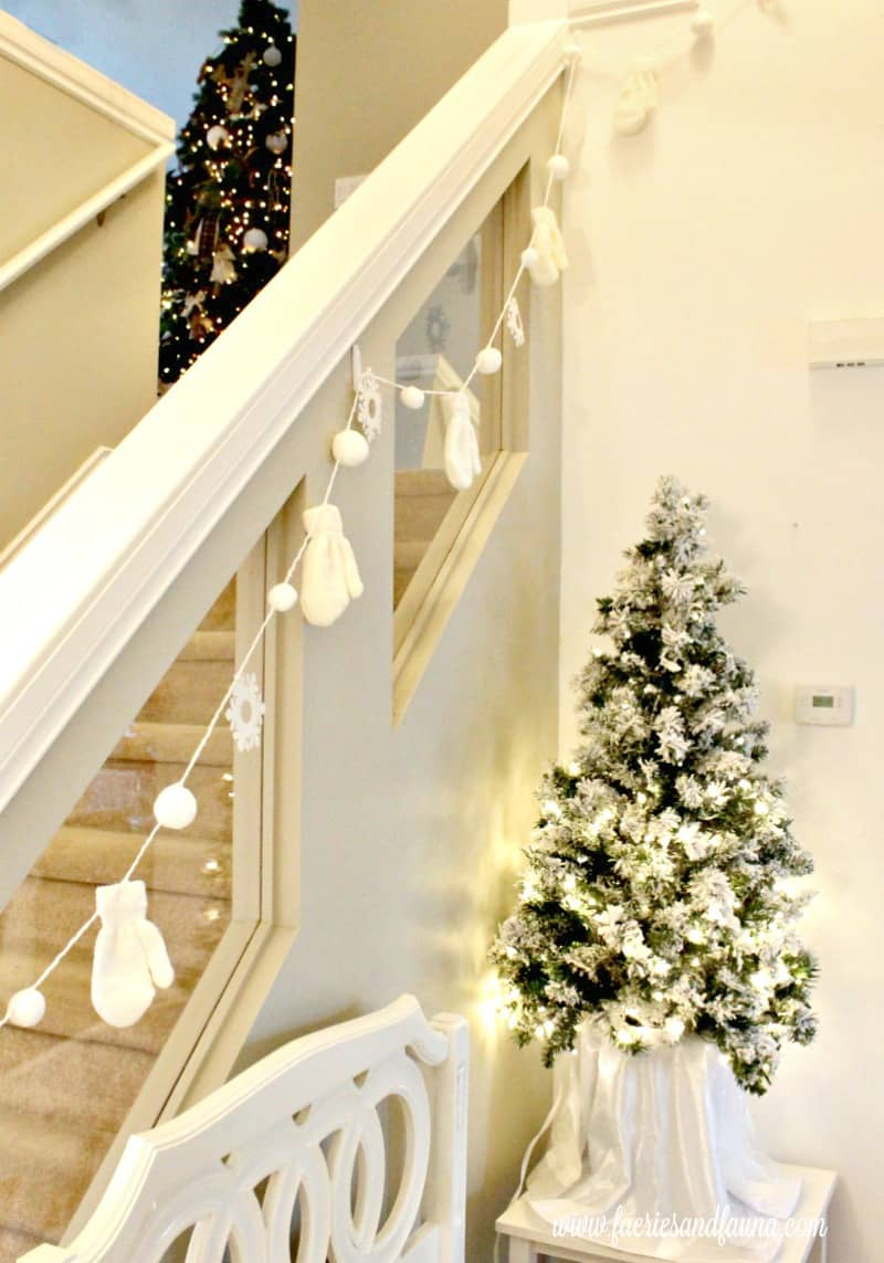 A Christmas tour banister with dollar store banner and two Christmas trees.
