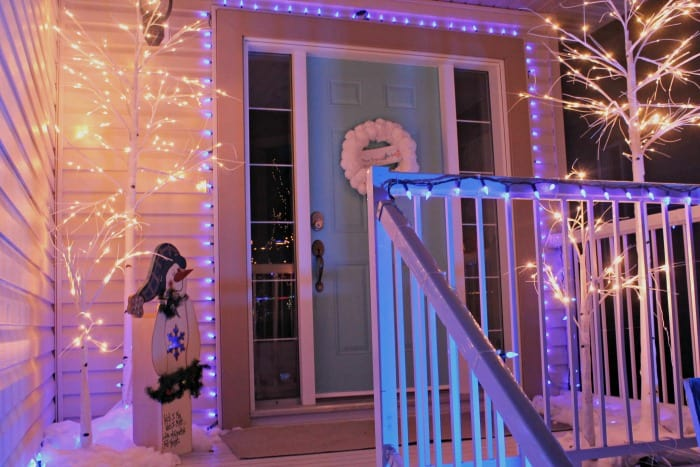 Front porch Christmas lights in blue and white, with blue Christmas light strings around the door and bright white Christmas trees. There is a litttle DIY snowman yard decorations flanking a Christmas door decorated with a DIY snowman wreath.