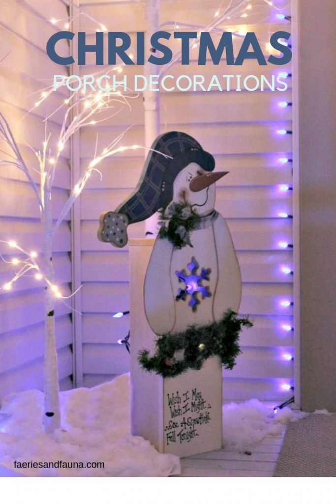 DIY Christmas porch decorations at night with blue and white lights and a wooden snowman.