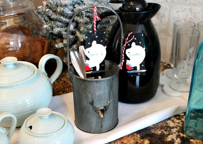 A hot cocoa bar with a tea pot, spoons in galvanized containers and decorated with little bear signs. hot chocolate bar,hot chocolate bar ideas, hot chocolate toppings,