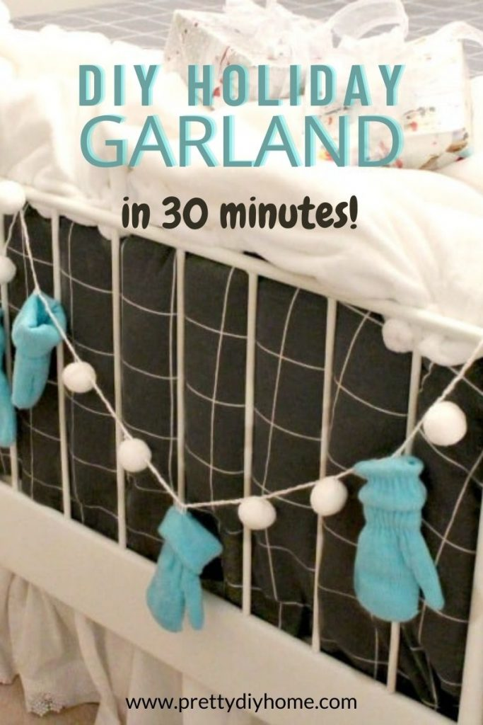 A blue and white mitten garland hanging on the end of a bed for Christmas decorating.
