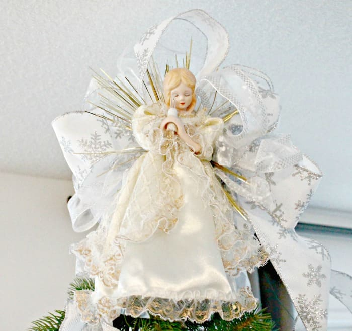 Christmas tree decorations ideas. A vintage white angel is added to a Christmas tree as it is a family tradition. ,  tree decorating ideas,Christmas tree decorations items
