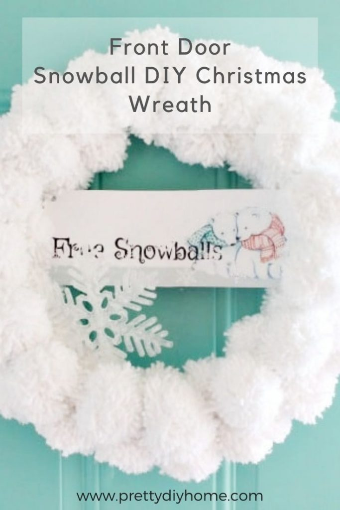 Easy Christmas Pom Pom Craft for adults and kids. A white and fluffy wool pom pom Christmas wreath hanging on a Christmas front door.