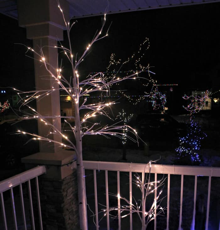 Exterior christmas decorating idea lighting up a Christmas porch with all kinds of pretty Christmas trees with white sparkly branches.