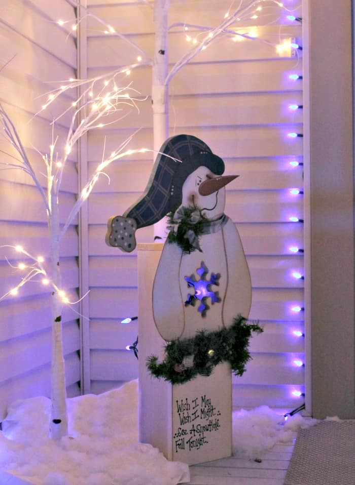 Homemade DIY wooden outdoor Christmas decorations at night. A DIY snowman yard decoration made from wood as an exterior Christmas decorating idea. The little snowman is lit up with pretty blue and white front porch Christmas lights.