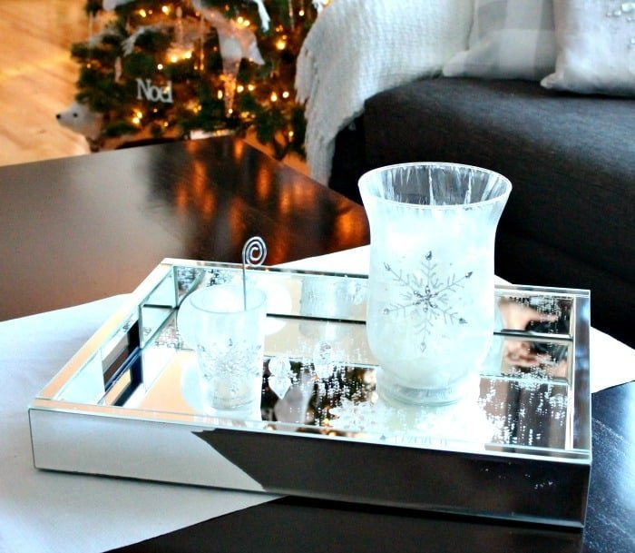 Easy DIY Centerpiece for Christmas, with white candles, snowflakes. a mirrored tray and glitter.