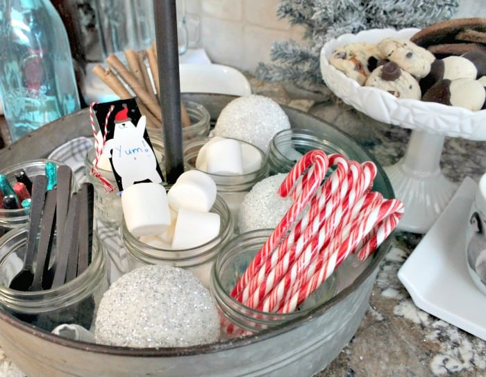 A hot cocoa bar with chocolate spoons, Christmas desserts, candy canes and marshmallows. A hot cocoa bar with a tea pot, spoons in galvanized containers and decorated with little bear signs. hot chocolate bar,hot chocolate bar ideas, hot chocolate toppings,