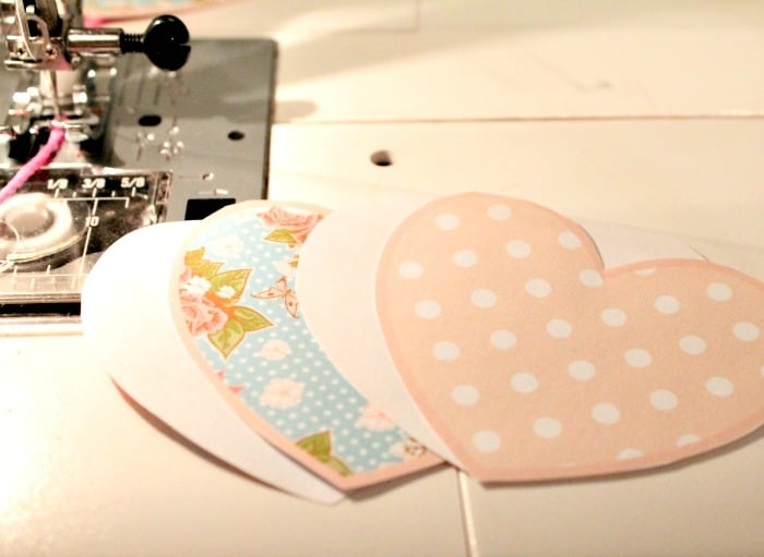 Cutting out and layering the paper Valentine banner pieces for an easy and cheap Valentine craft. A diy valentine banner free printables cut out for sewing.