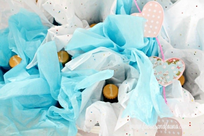 A bucket of craft beer wrapped up to look like flowers for a Valentines gift idea for him. A great men's valentines gift, Good valentines day gift for him with beer, and blue crepe paper.