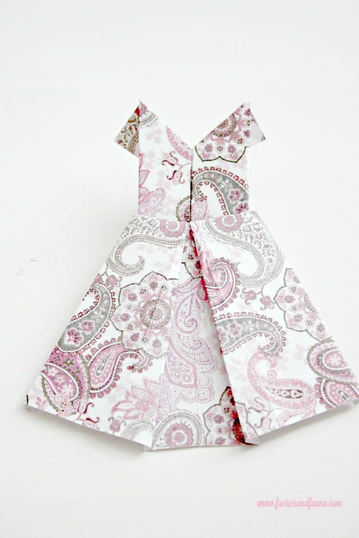 Close up picture of a paisley patterned pink scrap paper origami dress. DIYpaper banner, paper dress banner, paper dress design, spring banner, DIYspring decor, paper home decor, paper dress, banner