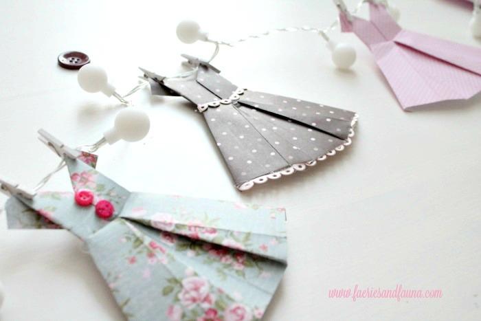 Folded paper dresses hung onto a light strand. origami dress, DIYpaper banner, paper dress banner, paper dress design, spring banner, DIYspring decor, paper home decor, paper dress, banner