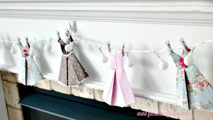Folded scrapbook paper turned into vintage dresses and hung on lights for a banner. Perfect for wedding showers, or little girls room. origami dress, DIY paper banner, paper dress banner, paper dress design, spring banner, DIY spring decor, paper home decor, paper dress, banner