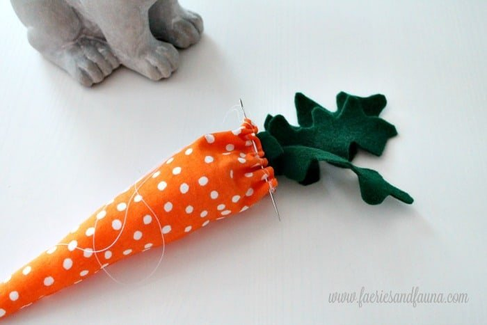 Attaching leaves to hand made stuffed carrots. A cute Spring craft or Easter craft idea for decorating.